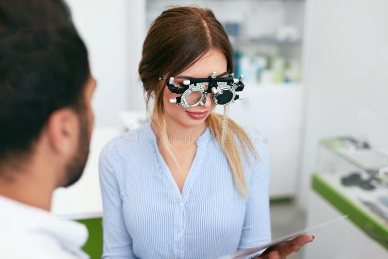 De Oogarts Checking Woman Eyesight van de optometrietest bij Kliniek stock afbeelding
