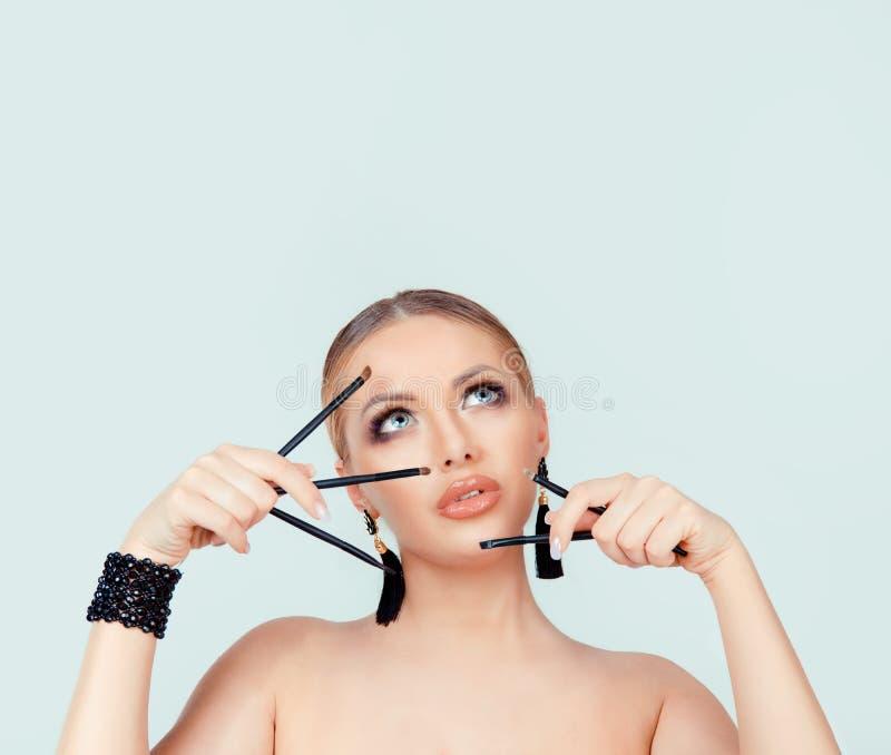 De oogschaduwborstels die van de vrouwenholding omhoog aan copyspace kijken royalty-vrije stock afbeelding
