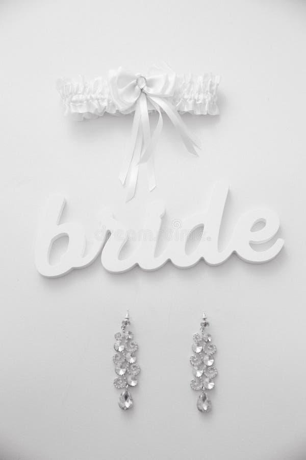 De oorringen en de kouseband van de bruid met woordbruid liggen op de witte lijst, BW stock foto's