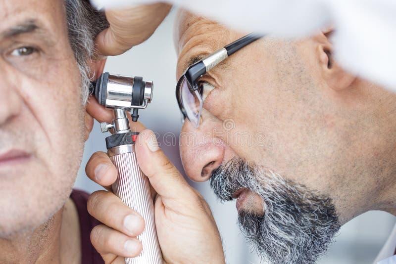 De oorspiegel van de artsenholding en het onderzoeken van oor van de hogere mens stock foto
