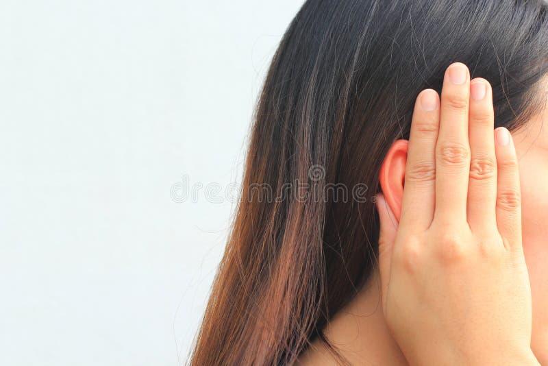 De oorsuizing, jonge vrouw heeft pijn in het oor royalty-vrije stock afbeelding
