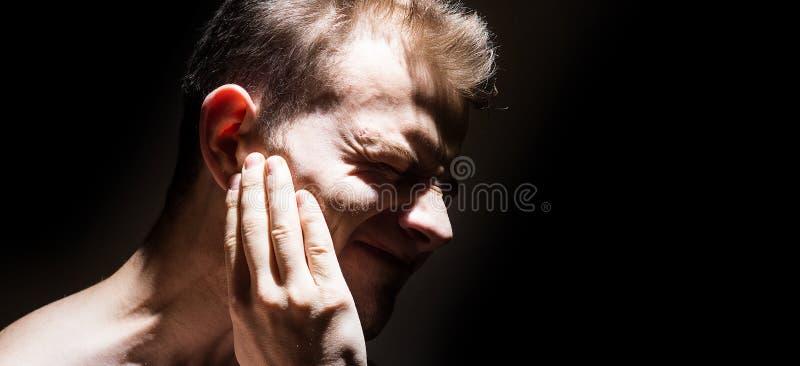De oorsuizing, mens op een zwarte achtergrond isoleerde het houden van een ziek oor, die aan pijn lijden royalty-vrije stock fotografie