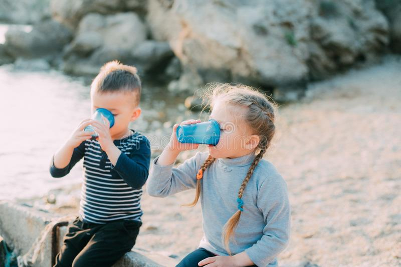 De de op zee kinderen, broer en de zuster drinken van plastic blauwe koppen van water of sap royalty-vrije stock fotografie