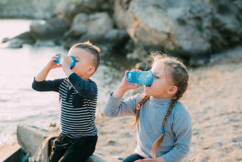 De de op zee kinderen, broer en de zuster drinken van plastic blauwe koppen van water of sap stock fotografie