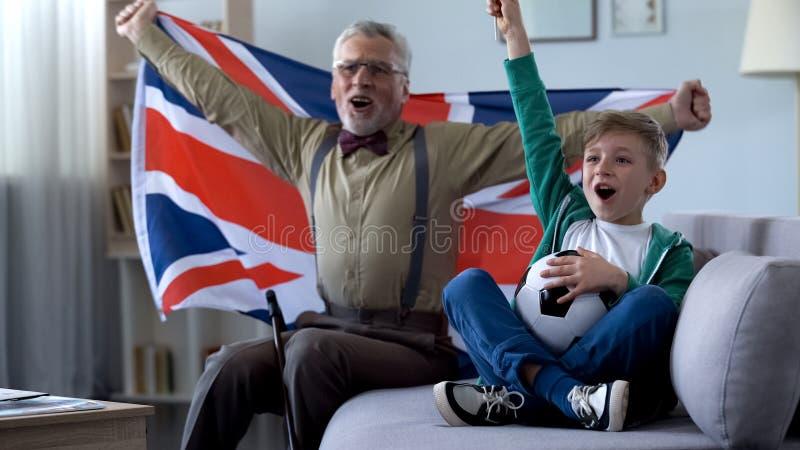 De opa die Britse vlag, samen met jongen golven viert overwinning van voetbalteam royalty-vrije stock foto's