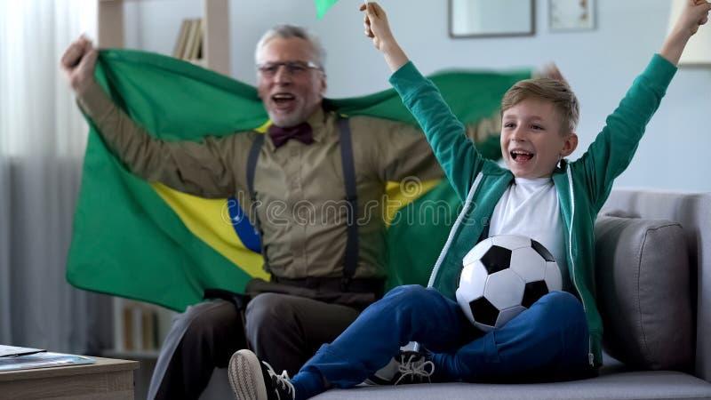 De opa die de vlag van Brazilië, samen met jongen golven verheugt zich overwinning van voetbalteam stock afbeeldingen