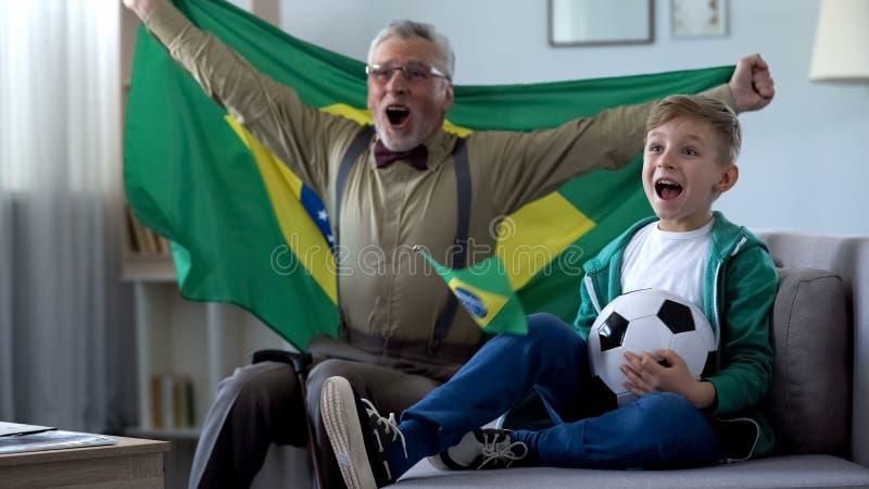 De opa die de vlag van Brazilië, samen met jongen golven viert overwinning van voetbalteam stock fotografie