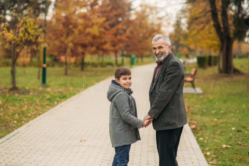 De opa en de kleinzoon brengen tijd in de herfstpark door Zij koesteren elkaar en gang Fmilytijd stock fotografie