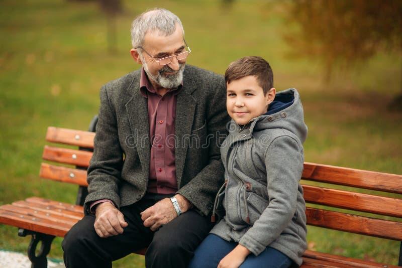 De opa en zijn kleinzoon brengen samen tijd in het park door Zij zitten op de bank royalty-vrije stock afbeelding