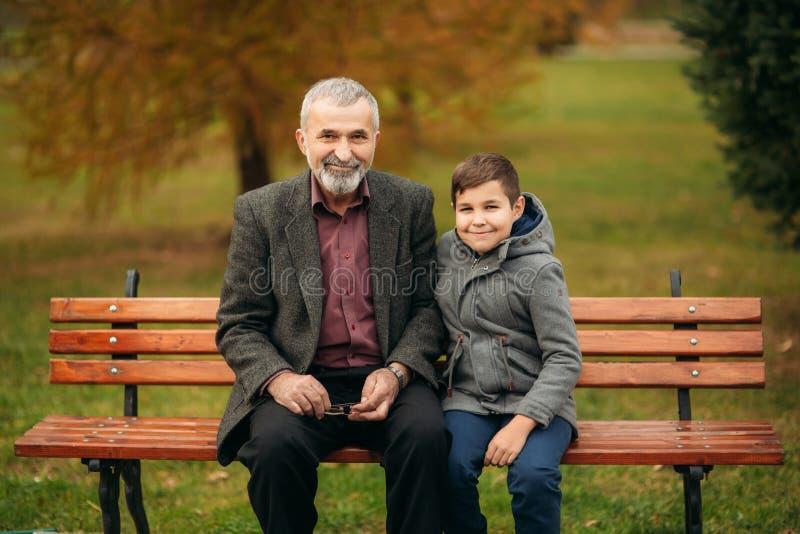 De opa en zijn kleinzoon brengen samen tijd in het park door Zij zitten op de bank stock foto's