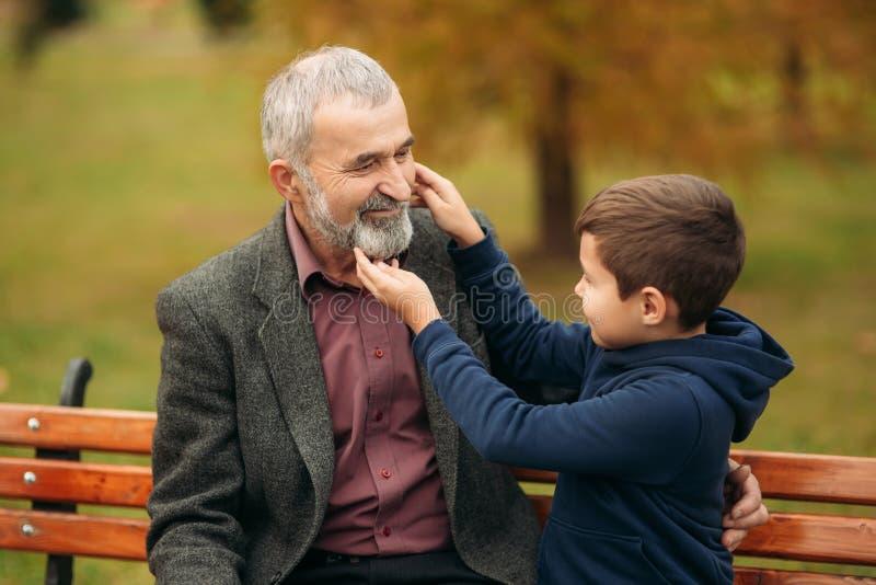 De opa en zijn kleinzoon brengen samen tijd in het park door Zij zitten op de bank Het lopen in het park en royalty-vrije stock foto's
