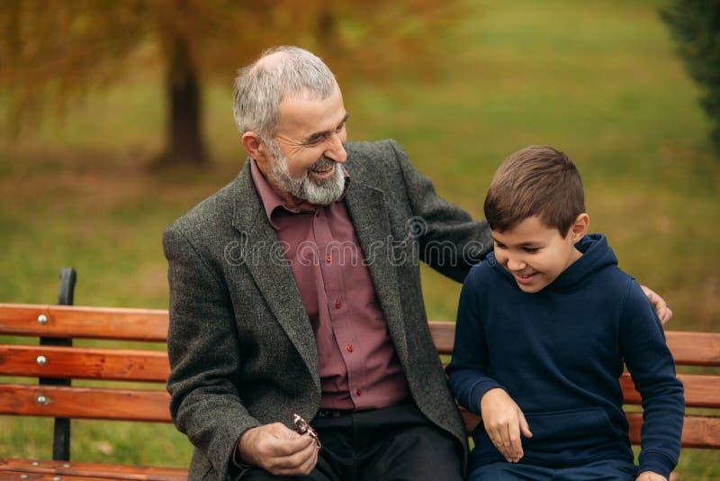 De opa en zijn kleinzoon brengen samen tijd in het park door Zij zitten op de bank Het lopen in het park en stock foto