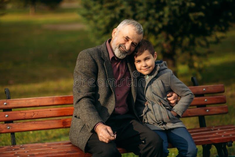De opa en zijn kleinzoon brengen samen tijd in het park door Zij zitten op de bank en de omhelzing elkaar stock fotografie