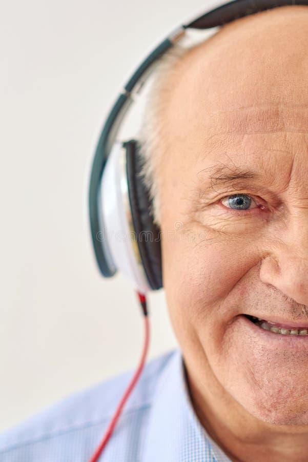 De opa luistert aan muziek stock foto