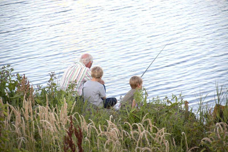 De opa onderwijst kleinkinderen visserij royalty-vrije stock afbeelding