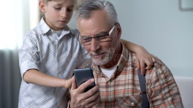 De opa van het jongensonderwijs om smartphone, digitale natie tegen oudere generatie te gebruiken royalty-vrije stock foto