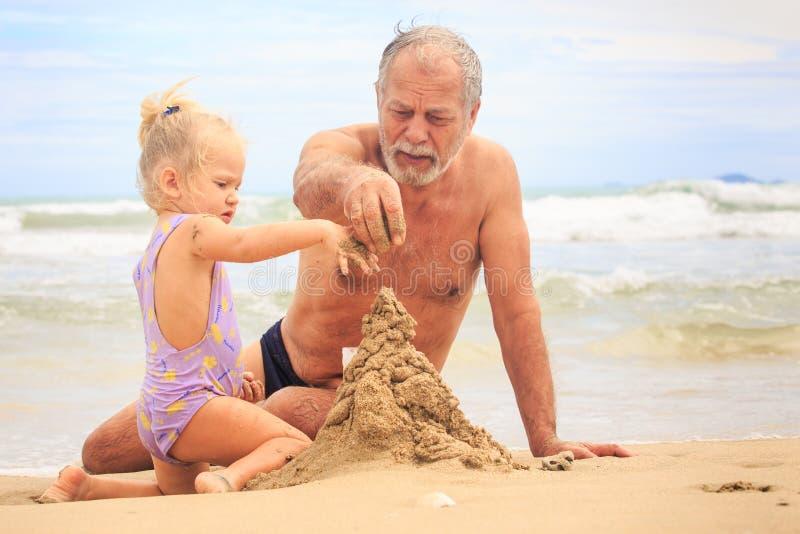 De opa Weinig Blonde Meisjesjongen bouwt Zandkasteel op Strand stock foto's