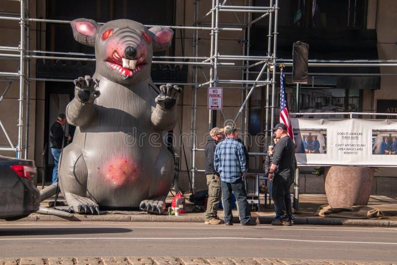 De opblaasbare rat wordt gezien op de stadsstraat voor een niet-verenigde dichtbij gezien bouwwerf met protestors royalty-vrije stock afbeeldingen