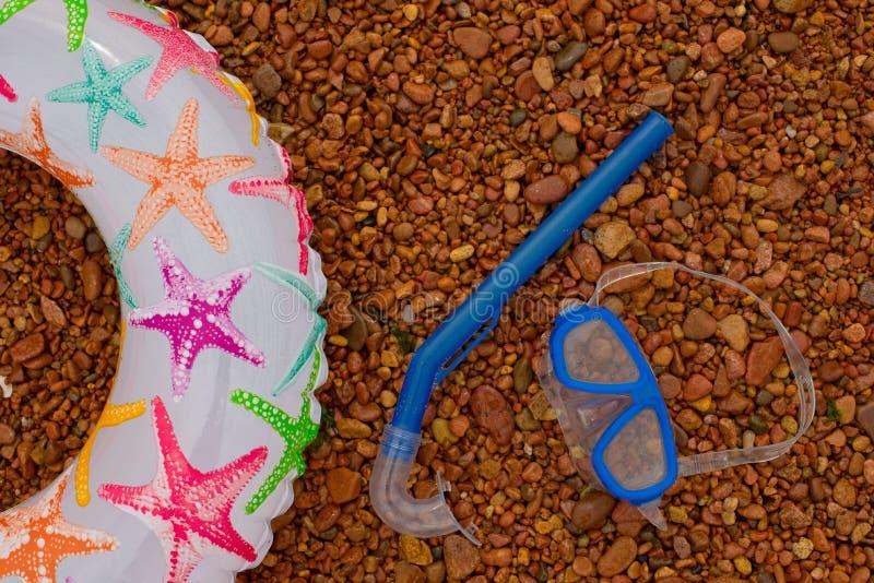 De opblaasbare ronde jonge geitjes het Onderwatermasker snorkelt, liggen op het strand royalty-vrije stock foto