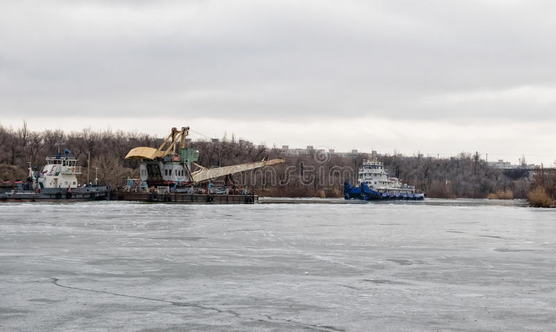 De opdringer van de riviersleepboot sleept een drijvende kraan door op een schipkanaal stock foto
