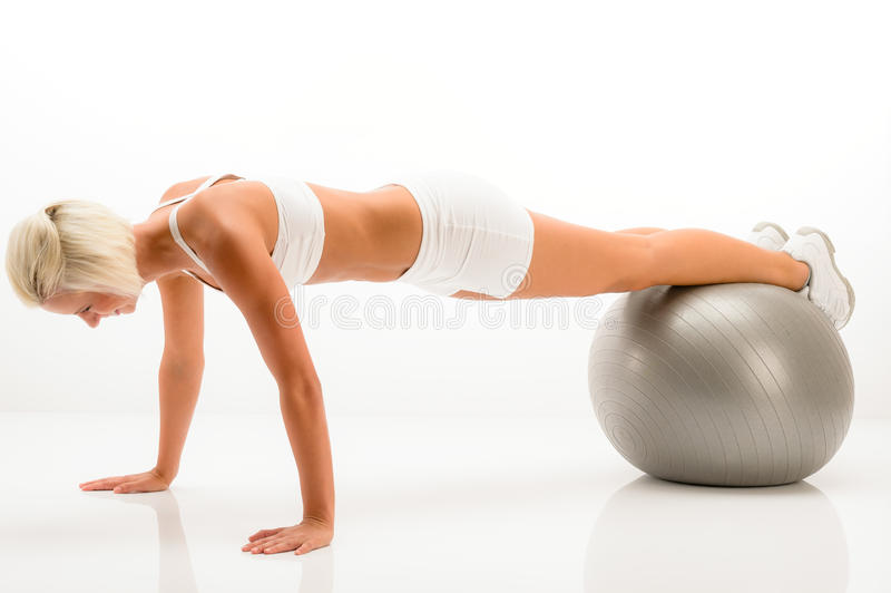 De opdrukoefeningen van de de gymnastiekbal van de vrouw bij witte geschiktheid royalty-vrije stock afbeeldingen