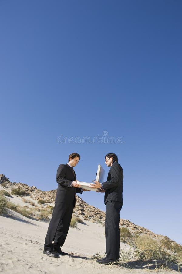 De Open Aktentas van de twee Zakenliedenholding in de Woestijn stock foto's
