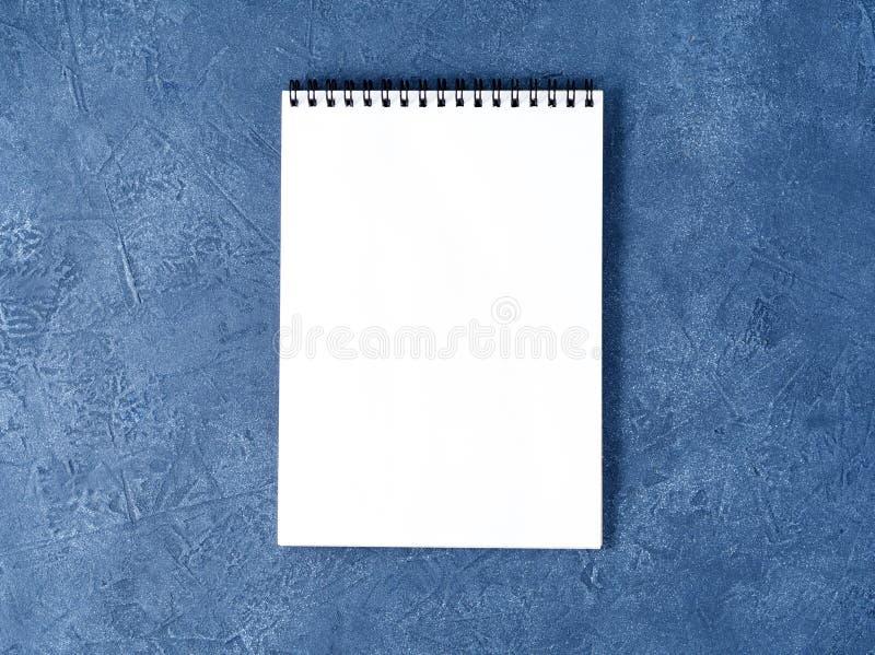 De open blocnote met schone witte pagina op oude donkerblauwe steenlijst, hoogste mening stock foto's