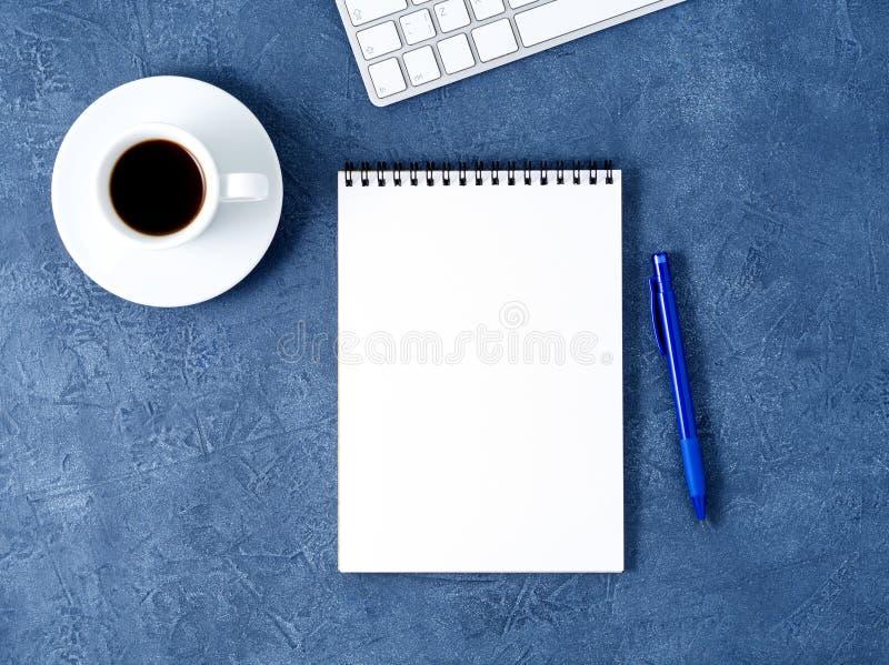 De open blocnote met schone witte pagina, de pen en de koffie vormen op oude donkerblauwe steenlijst tot een kom, hoogste mening stock afbeeldingen