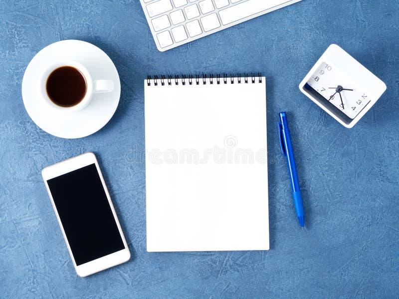De open blocnote met schone witte pagina, de pen en de koffie vormen op oude donkerblauwe steenlijst tot een kom, hoogste mening royalty-vrije stock afbeelding