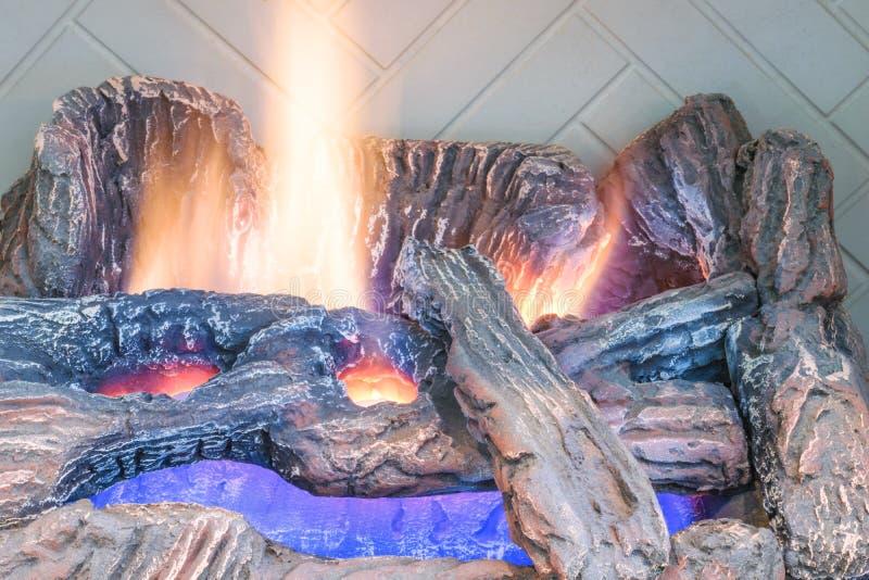 De open haardlogboeken van het close-upgas met gloeiende vlammen stock foto