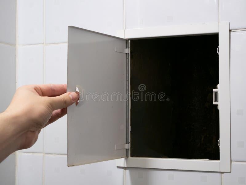 De open kleine deur van de loodgieterhand aan badkamerspijpen stock afbeeldingen