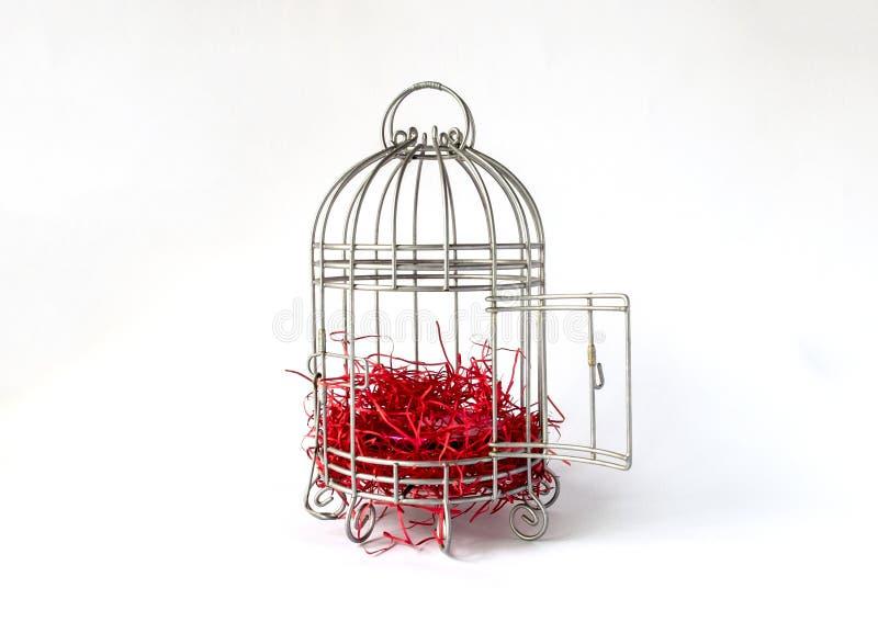 De open Kooi van de Staalvogel met Stukken van Rood die Document als Nest op Witte Achtergrond worden geïsoleerd stock fotografie
