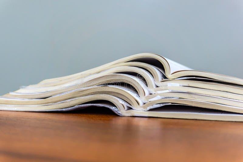 De open tijdschriften liggen bovenop elkaar op een bruine lijst, zijn de documenten gestapeld close-up royalty-vrije stock foto's
