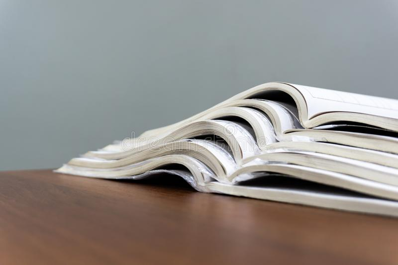 De open tijdschriften liggen bovenop elkaar op een bruine lijst, zijn de documenten gestapeld close-up stock fotografie