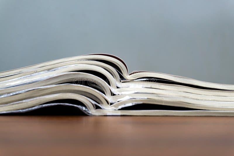 De open tijdschriften liggen bovenop elkaar op een bruine lijst, zijn de documenten gestapeld close-up stock afbeelding