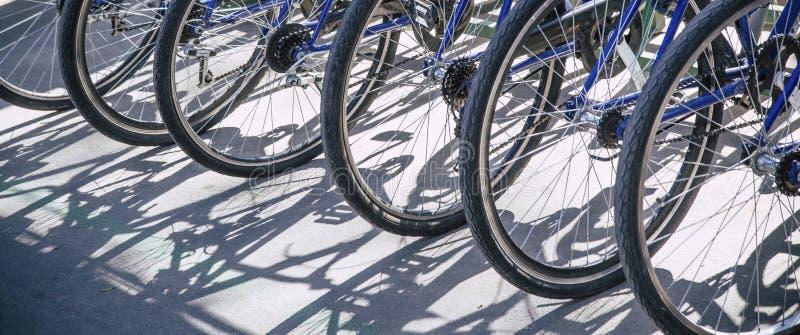 de Openbare fietsen van de fietshuur, die fietsenzadel delen Detailmening van een fietswiel met meer opgestelde fietsen Fietshuur stock afbeeldingen