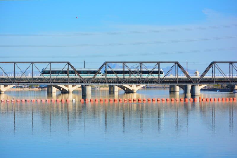 De openbare Trein die van het Doorgangs Lichte Spoor Brug over Water kruisen stock fotografie