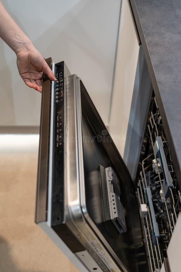 De openingsdeur van de vrouwenhand in nieuwe moderne ingebouwde afwasmachine stock foto's