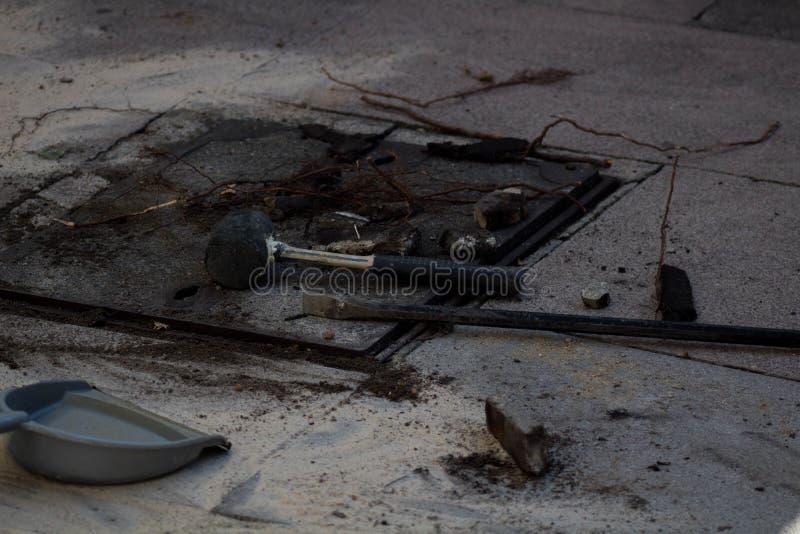 De openlucht grijze bestrating van de steenstraat, met uit geplaatste hulpmiddelen en puin, dat onlangs is gewerkt aan stock foto's