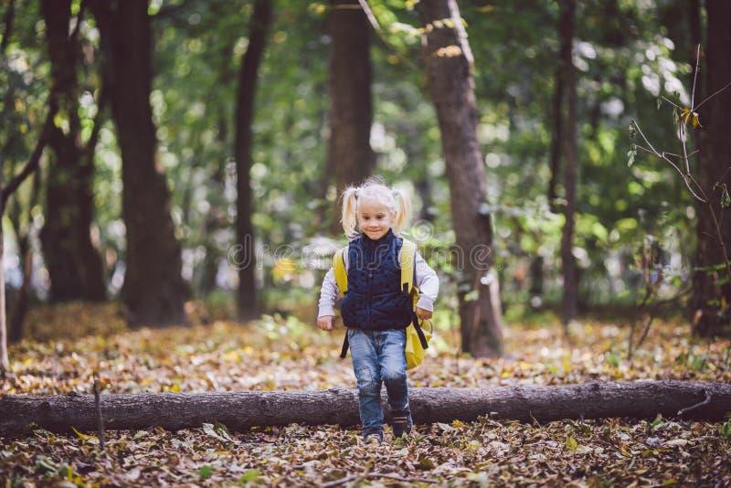 De openluchtactiviteiten van themakinderen De grappige gangen die van weinig baby Kaukasische blonde meisje door bos hindernissen royalty-vrije stock afbeelding