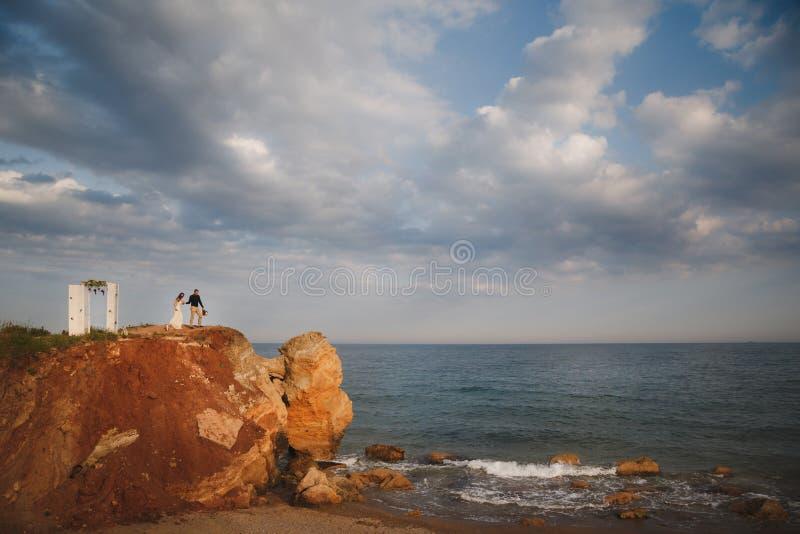 De openluchtceremonie van het strandhuwelijk dichtbij de oceaan, huwelijkspaar bevindt zich dichtbij het huwelijksaltaar op rots  stock fotografie