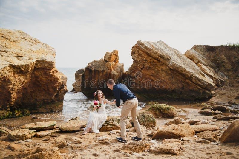 De openluchtceremonie van het strandhuwelijk dichtbij de oceaan, romantische gelukkige paarzitting op stenen bij het strand royalty-vrije stock fotografie