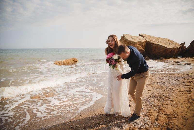 De openluchtceremonie van het strandhuwelijk dichtbij het overzees, de modieuze gelukkige glimlachende bruidegom en de bruid hebb stock foto