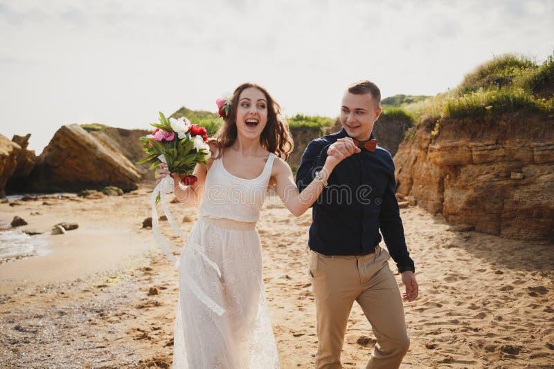 De openluchtceremonie van het strandhuwelijk dichtbij het overzees, de modieuze gelukkige glimlachende bruidegom en de bruid hebb royalty-vrije stock foto's