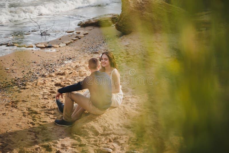 De openluchtceremonie van het strandhuwelijk, modieus huwelijks houdend van paar zit dichtbij het overzees stock afbeeldingen