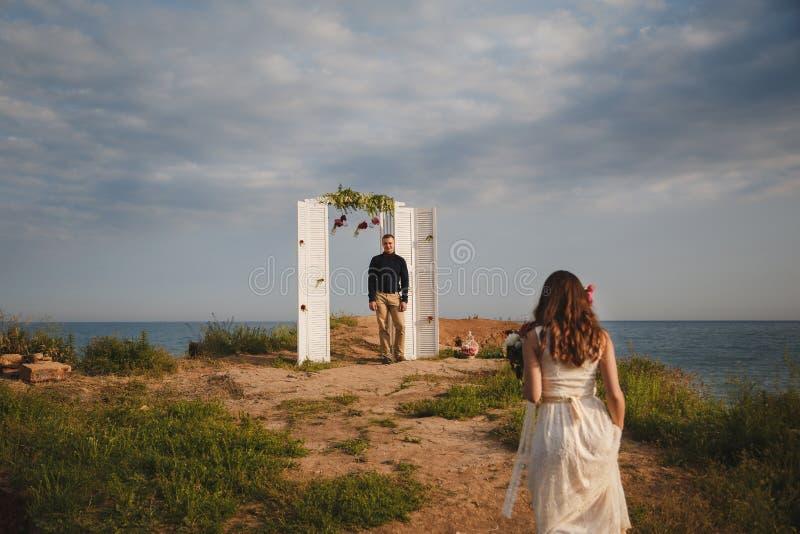 De openluchtceremonie van het strandhuwelijk, modieuze gelukkige bruidegom bevindt zich dichtbij huwelijksboog op de overzeese ku stock foto