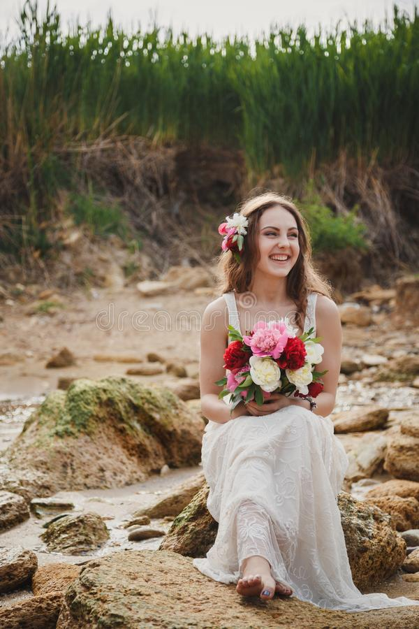 De openluchtceremonie van het strandhuwelijk, modieuze gelukkige het glimlachen bruidzitting op stenen en het lachen stock foto