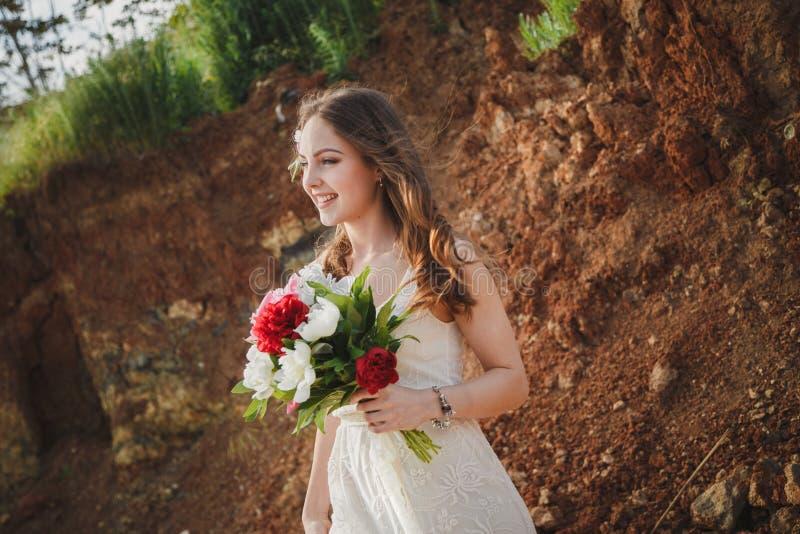 De openluchtceremonie van het strandhuwelijk, modieuze gelukkige glimlachende bruid met boeket van bloemen stock foto