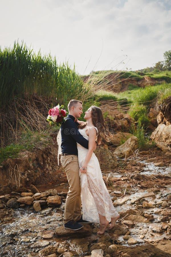 De openluchtceremonie van het strandhuwelijk, de modieuze gelukkige glimlachende bruidegom en de bruid kussen dichtbij kleine riv royalty-vrije stock afbeeldingen