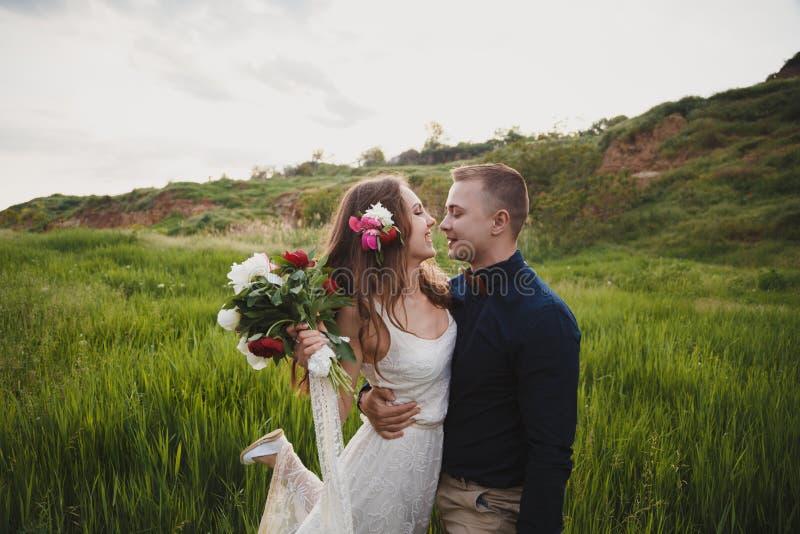 De openluchthuwelijksceremonie, de modieuze gelukkige glimlachende bruidegom en de bruid koesteren en bekijken elkaar Het ogenbli royalty-vrije stock foto